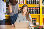Woman With Laptop Sitting At Table In College Library — Stockfoto