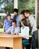 Students And Teacher Looking At Digital Tablet In Classroom — Stock Photo