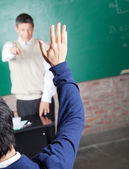 Student Raising Hand To Answer Question In Classroom — Stock Photo