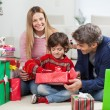 Stock Photo: WomWith Boy And MOpening Christmas Gift