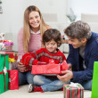 Woman With Boy And Man Opening Christmas Gift — Stock Photo