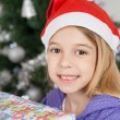 Stock Photo: Girl Wearing SantHat With Christmas Gift