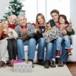 Stock Photo: Family With Christmas Presents Sitting On Sofa