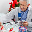 Man Wrapping Christmas Present — Stock Photo