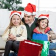 Siblings Sitting On Father's Lap With Christmas Presents — Stockfoto