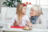 Grandmother And Girl With Cardpaper Looking At Each Other — Stock Photo