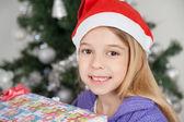 Girl Wearing Santa Hat With Christmas Gift — Stock Photo