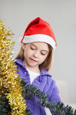 Girl Looking At Tinsels During Christmas — Stock Photo