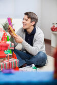Smiling Man Holding Christmas Presents At Home — Stock Photo