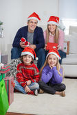 Family In Santa Hats At Home During Christmas — Stock Photo