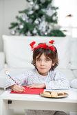 Boy Wearing Headband Writing Letter To Santa Claus — Stock Photo