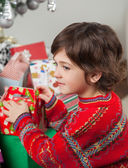 Boy Stacking Christmas Gifts — Stock Photo