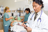 Doctor Writing Notes in Emergency — Stockfoto
