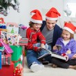 Siblings And Father Reading Book By Christmas Presents — Stock Photo #33963109