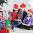 Siblings And Father Reading Book By Christmas Presents — Stock Photo