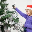 Foto Stock: Girl Decorating Christmas Tree With Fairy Lights