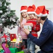 Parents Giving Gift To Boy By Christmas Tree — Stock Photo #33963809