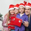 Parents And Children With Christmas Gift — Photo