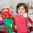 Boy Sitting By Stacked Christmas Presents — Stock Photo #33963945