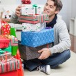 Stock Photo: Smiling MWith Stack Of Christmas Gifts