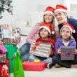 Stock Photo: Family In SantHats Sitting By Christmas Presents