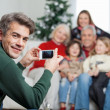 Father Photographing Family Through Mobilephone During Christmas — Stock Photo #33966599