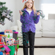 Girl Holding Fairy Lights While Standing By Christmas Presents — Stock Photo