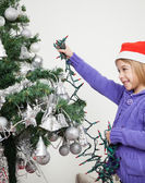 Girl Decorating Christmas Tree With Fairy Lights — Stock Photo