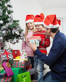 Parents Giving Gift To Boy By Christmas Tree — Stok fotoğraf