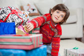 Boy Taking Christmas Gift From Stack — Stok fotoğraf