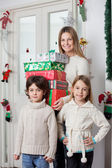 Family With Gifts Standing By Door During Christmas — Stock Photo