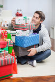 Smiling Man With Stack Of Christmas Gifts — Стоковое фото