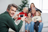 Father Photographing Family Through Mobilephone During Christmas — Stock Photo