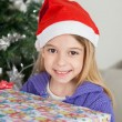Smiling Girl In Santa Hat Holding Christmas Gift — Stock Photo