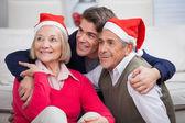 Liefdevolle zoon met ouders dragen santa hoeden — Stockfoto