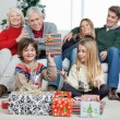 Boy Holding Christmas Gift With Family In House — Stock Photo