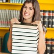 Beautiful Woman With Piled Books Smiling In Library — Stock Photo
