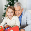 Girl And Grandfather With Christmas Gifts — Stock Photo #34003337