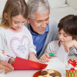 Smiling Man Assisting Children In Making Greeting Card — Stock Photo #34003795