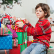 Cute Boy Kneeling By Christmas Gifts — Stock Photo