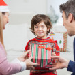 Boy Receiving Christmas Gift From Parents — Stockfoto