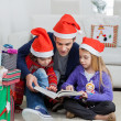 Father And Children In Santa Hats Reading Book — Stock Photo #34004579