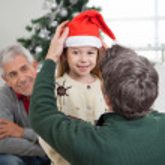 Father Adjusting Girl's Santa Hat — Stock Photo #34004703