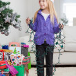 Girl Holding Fairy Lights While Standing By Christmas Gifts — Stock Photo