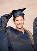 Woman In Graduation Gown Holding Mortar Board On Campus — Stock Photo