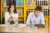 Student Studying While Friend Using Mobilephone In Library — Stock Photo