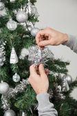 Человек, украшающий рождественскую елку — Стоковое фото