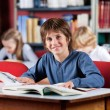 Schoolboy Smiling With Books At Table In Library — Stock Photo