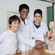 Stock Photo: Teacher Pointing At Anatomical Model With Students At Desk