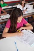 Genç liseli kız masa başında yazma — Stok fotoğraf